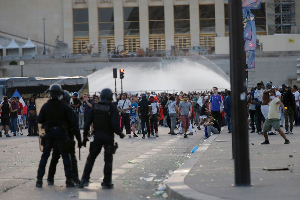 French riot police face off with youths during clashes near the Paris fan zone.