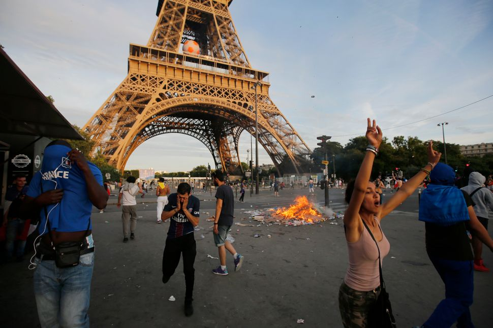 Garbage burns during clashes near the Paris fan zone at the Eiffel Tower.