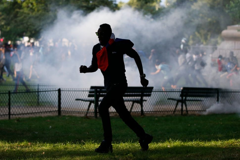 A man runs near tear gas close to the Euro fan zone.