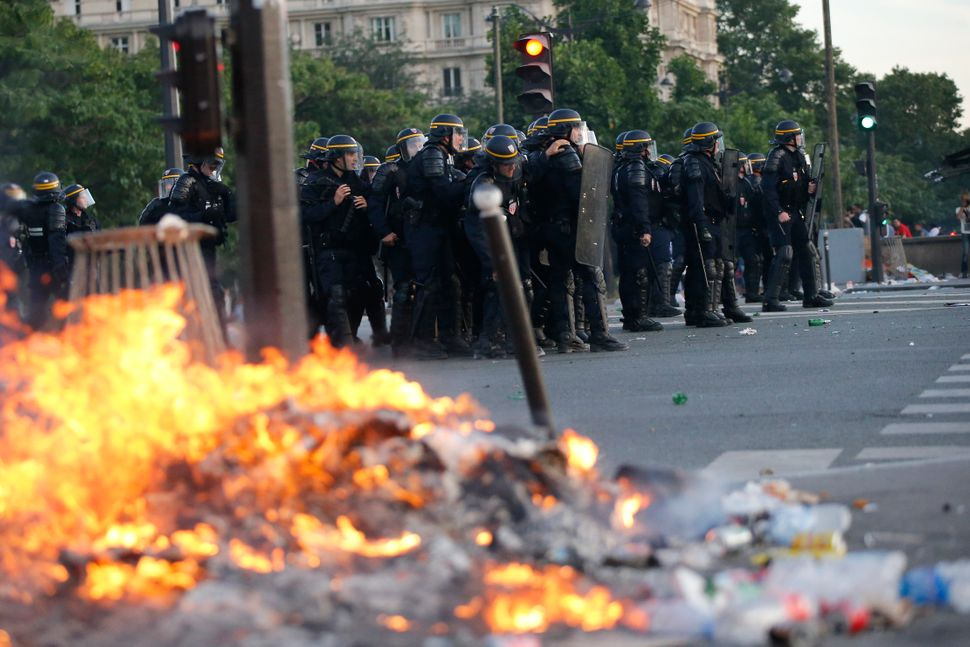 Garbage burns near French CRS riot police who secured the area.