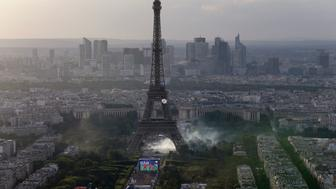 TOPSHOT - A picture taken from the Tour Montparnasse shows tear gas under the Eiffel tower during clashes between police and supporters trying to illegally enter the Champs de Mars fan zone on July 10, 2016 in Paris, before the Euro 2016 football tournament final match between Portugal and France. / AFP / Thomas SAMSON        (Photo credit should read THOMAS SAMSON/AFP/Getty Images)