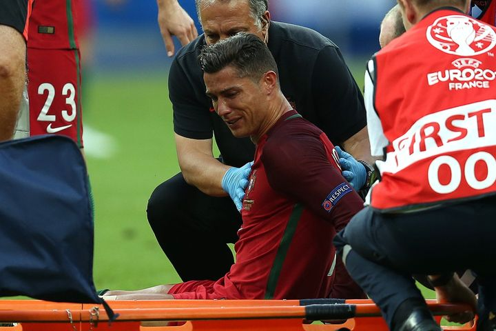 Cristiano Ronaldo of Portugal sheds tears as he waits to be carried off on a stretcher during the UEFA Euro 2016 final match