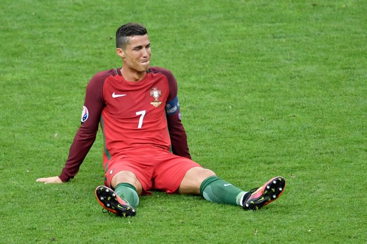 Portugal's forward Cristiano Ronaldo reacts after an injury following a clash with France's forward Dimitri Payet.