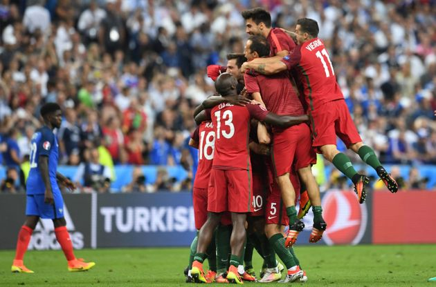 Portugal players celebrate after they scored a goal during the Euro 2016 final football match between...