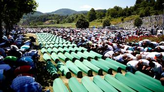 Muslim men pray in front of coffins during mass funeral in Potocari near Srebrenica, Bosnia and Herzegovina July 11, 2016. REUTERS/Dado Ruvic TPX IMAGES OF THE DAY