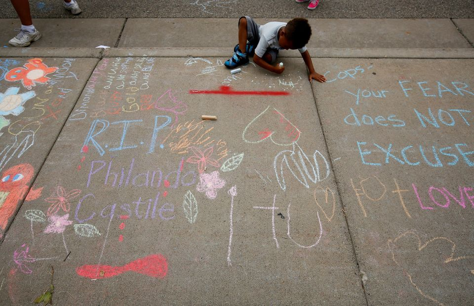 A boy sits near messages written in chalk as demonstrators protesting the shooting death of Philando Castile gather in front