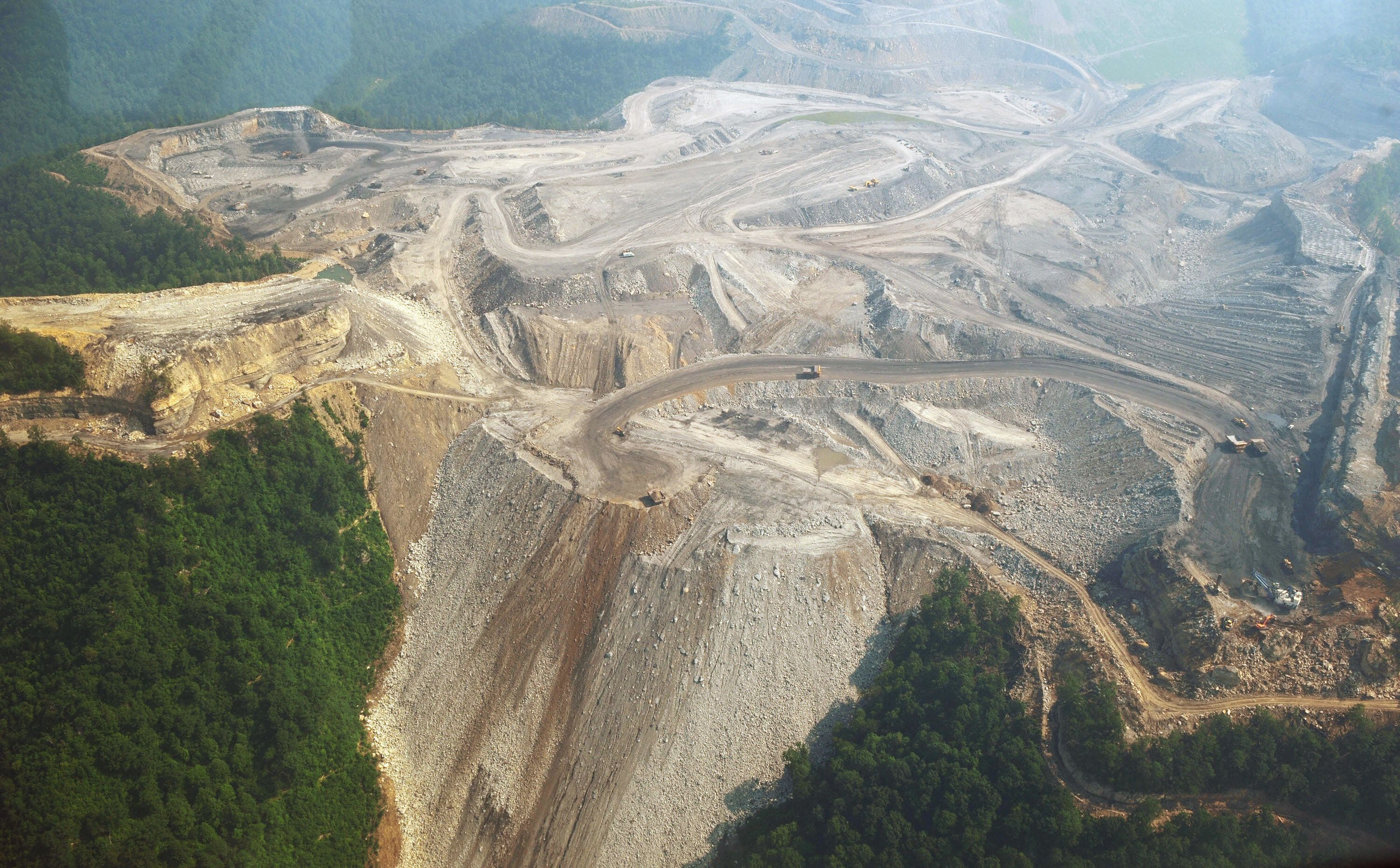 TO GO WITH AFP STORY by Virginie MONTET, USA-environment-energy-pollution A June 13, 2008 photo shows  a large mountaintop coal mining operation in West Virginia. Mountaintop removal mining (MTR), referred to in coal the industry as mountaintop mining/valley fills is surface mining involving extreme change to the summit or summit ridge of a mountain. It is used mainly with coal mining in the Appalachian Mountains, in the eastern US. The process involves using explosives to remove up to 1,000 vertical feet (304.8 meters) of rock to get to the coal. The debris is often moved into the adjacent river valleys, called a valley fill.    AFP PHOTO/Mandel NGAN (Photo credit should read MANDEL NGAN/AFP/Getty Images)