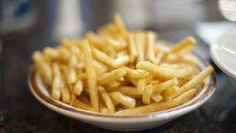 Plates of french fries in diner setting.