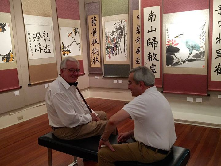 Visitors to Nan Liu's exhibition with examples of his brush paintings.