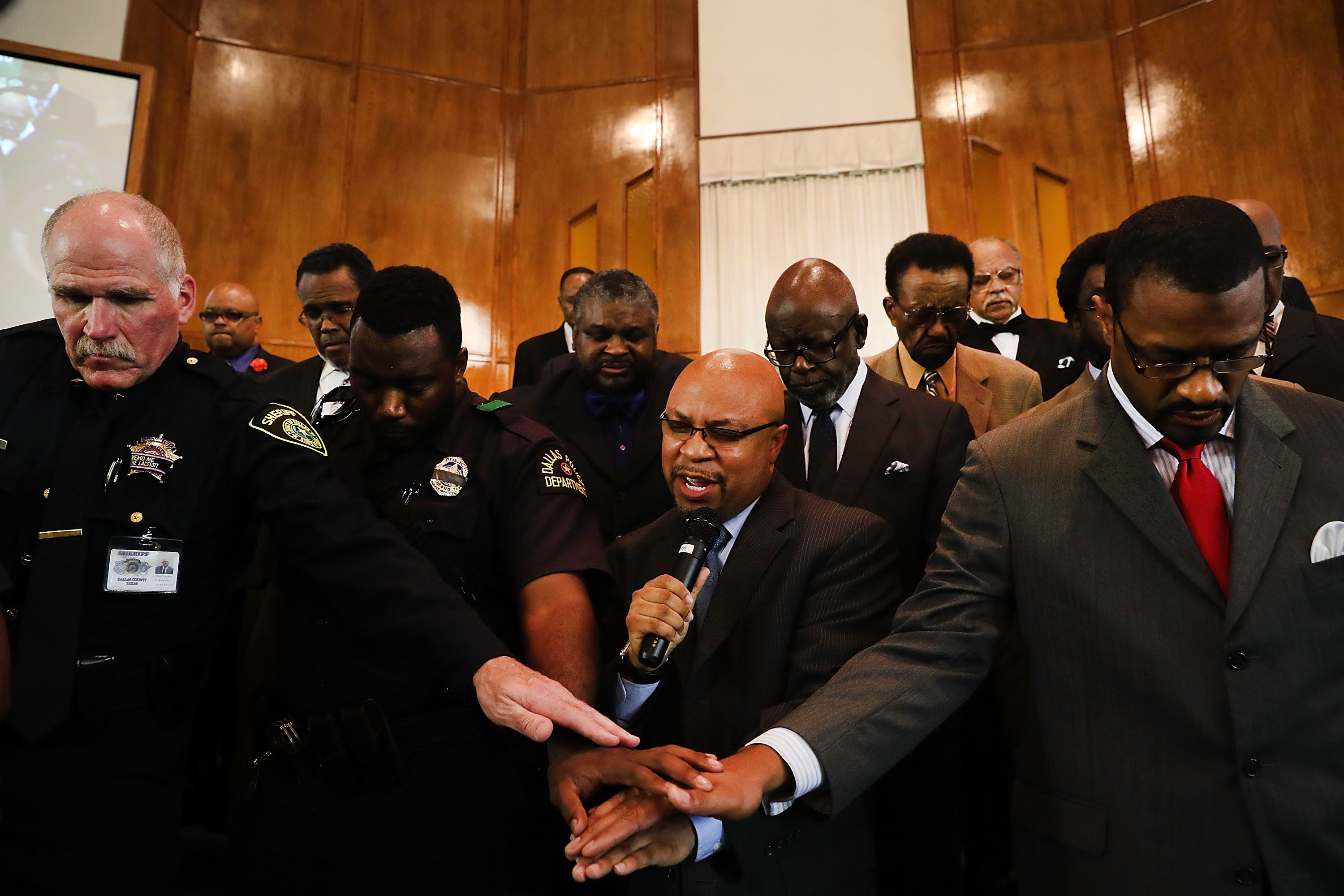 DALLAS, TX - JULY 10: Police officers from area departments in and around Dallas pray with Minister Carl Sherman at a multicurtural prayer vigil on July 10, 2016 in Dallas, Texas. The service at the Dallas Area Interfaith Church drew over 100 worshippers including police officers. Five Dallas police officers were killed and seven others were injured last Thursday night in an evening ambush during a march against recent police involved shootings. Investigators say the suspect is 25-year-old Micah Xavier Johnson of Mesquite, Texas. This is the deadliest incident for U.S. law enforcement since September 11.  (Photo by Spencer Platt/Getty Images)