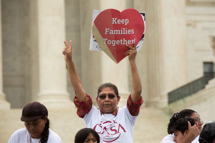 Antonia Surco, originally from Peru, holds a sign in front of the Supreme Court onthe day the justices split 4-to-4 on
