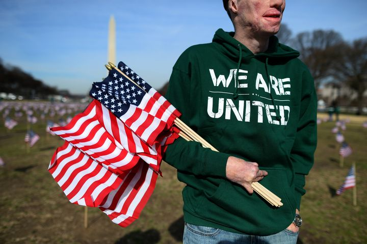 US Marine Corps Cpl. Aaron Mankin helps set up 1,892 American flags on the National Mall in Washington, DC, on March 27, 2014