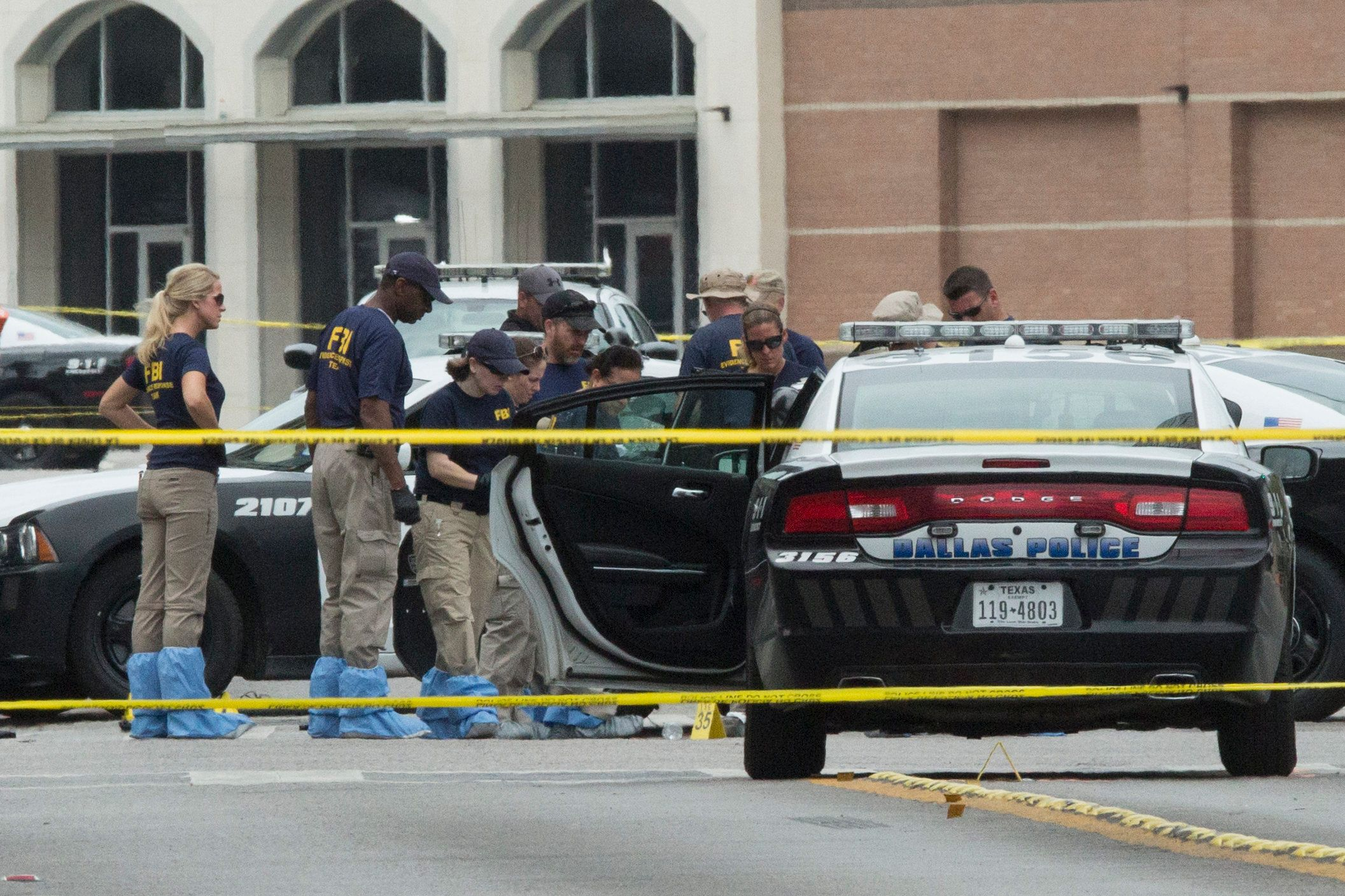 FBI agents examine the crime scene of the Dallas, Texas, sniper shooting on July 9, 2016. The e gunman behind a sniper-style attack in Dallas was an Army veteran and loner driven to exact revenge on white officers after the recent deaths of two black men at the hands of police, authorities have said. Micah Johnson, 25, had no criminal history, Dallas police said in a statement.  / AFP / Laura Buckman        (Photo credit should read LAURA BUCKMAN/AFP/Getty Images)