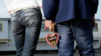 Teenage couple (14-16) holding hands, mid section, rear view