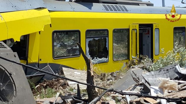 A damaged passenger train is seen after a collision with another in the middle of an olive grove in the...