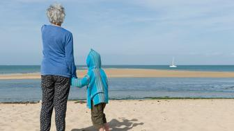 Grandmother and grandson standing together on beach, looking at boat on horizon