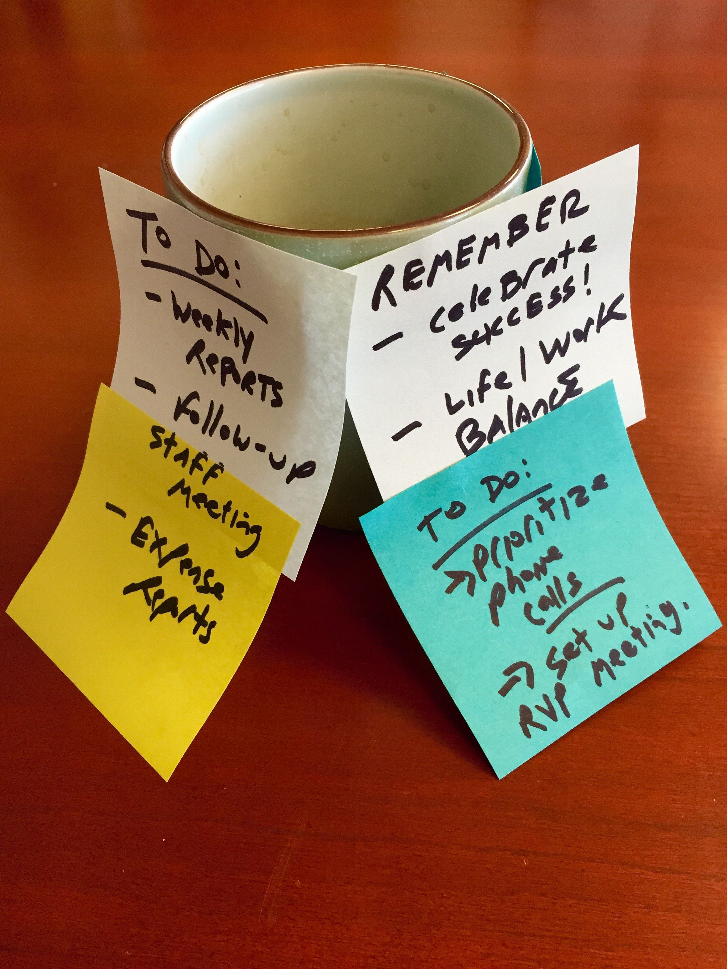 Hand-written sticky notes on a coffee mug on a wood desktop