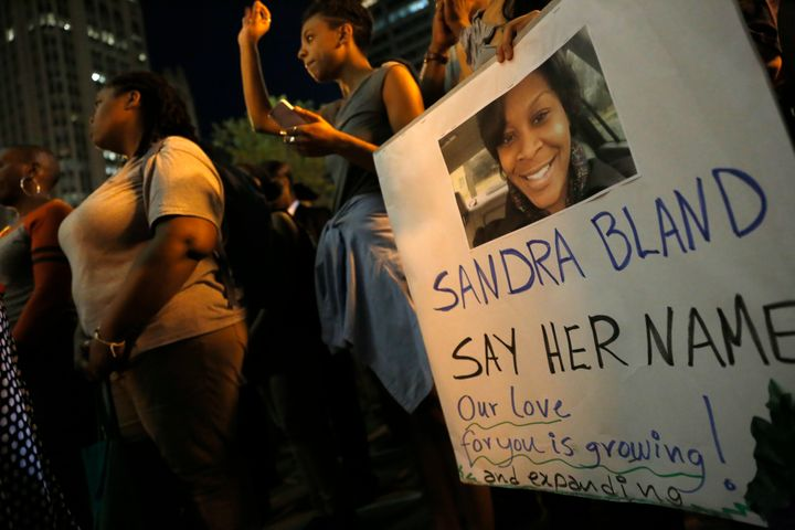 A demonstrator holds a Sandra Bland sign during a vigil in July 2015.