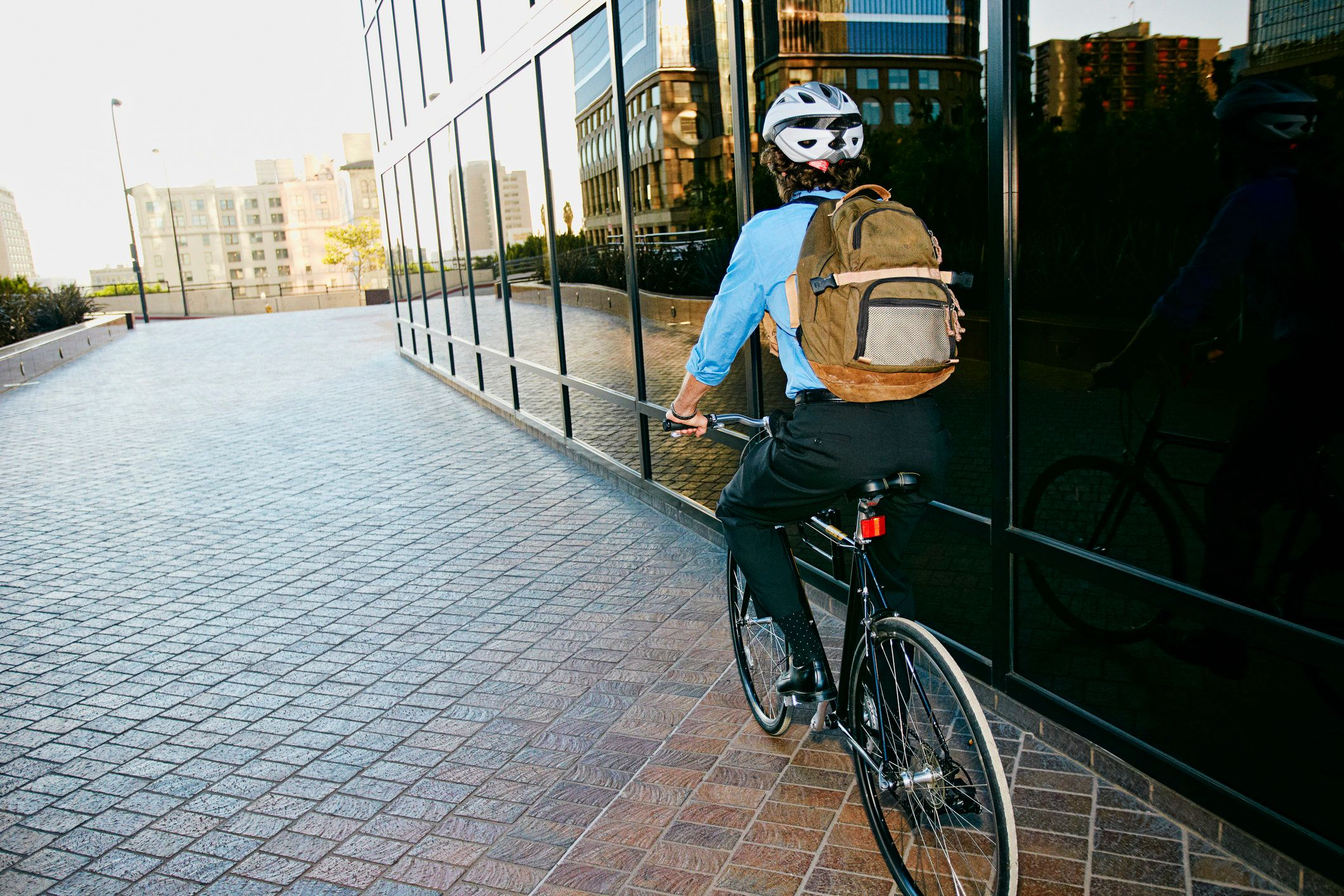 Caucasian businessman riding bicycle outside building