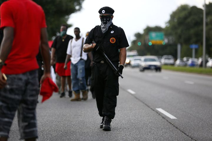 A demonstrator wearing the insignia of the New Black Panthers Party carries a shotgun during a protest over the shooting deat