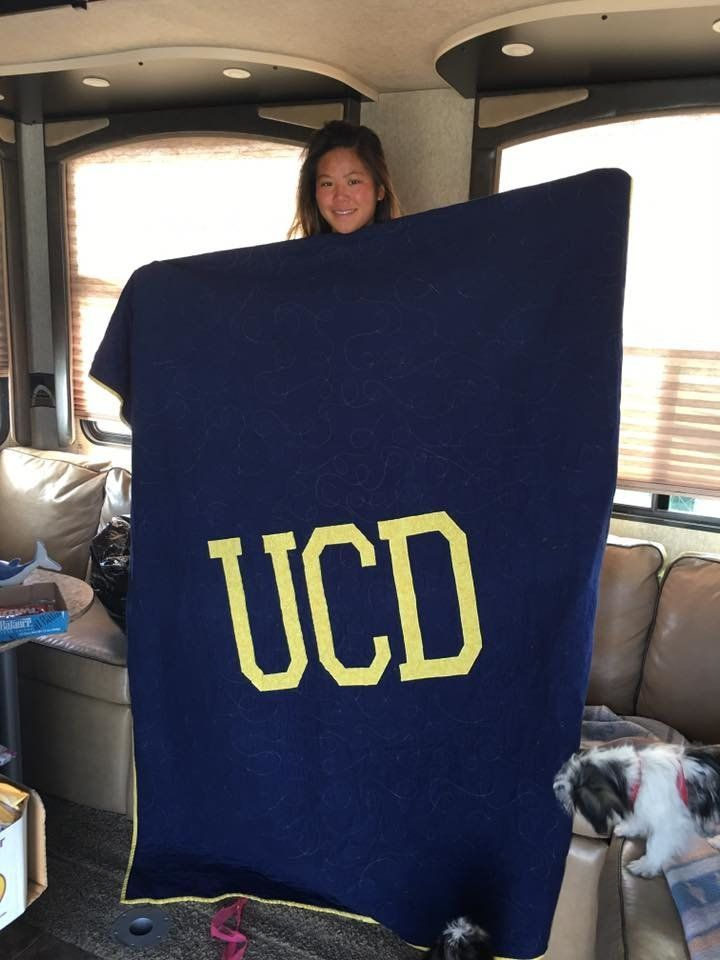 Sulyn Harvey holds up the back side of the memory quilt. She is headed to University of California, Davis.