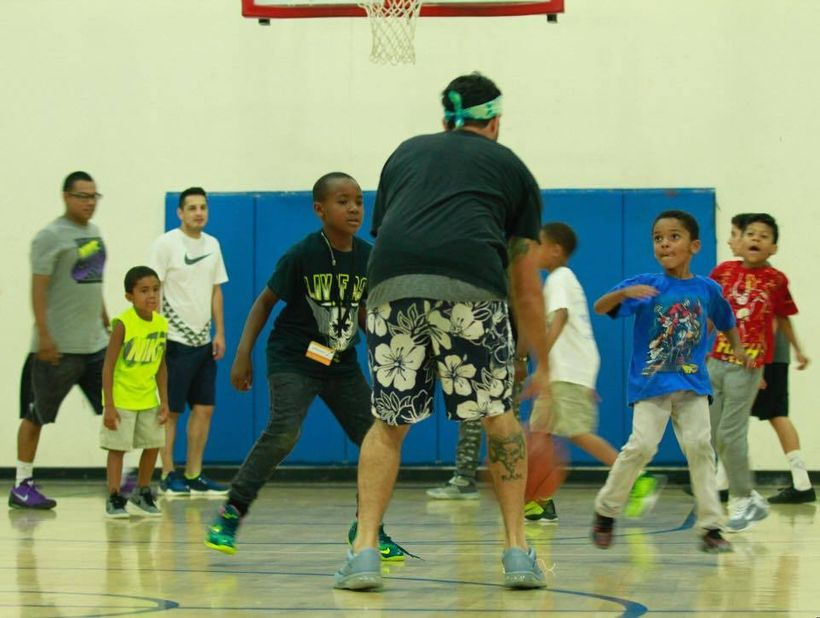 Rikki Mendias playing ball in his old gym with PAL kids