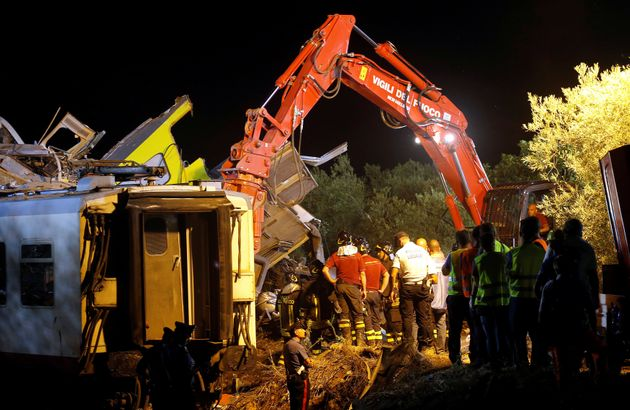 Rescuers work at the site where two passenger trains collided in the middle of an olive grove in the...