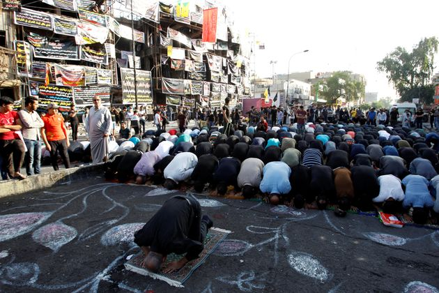Sunni and Shi'ite Muslims attend prayers in Baghdad on July 6 during Eid al-Fitr as they mark the end...