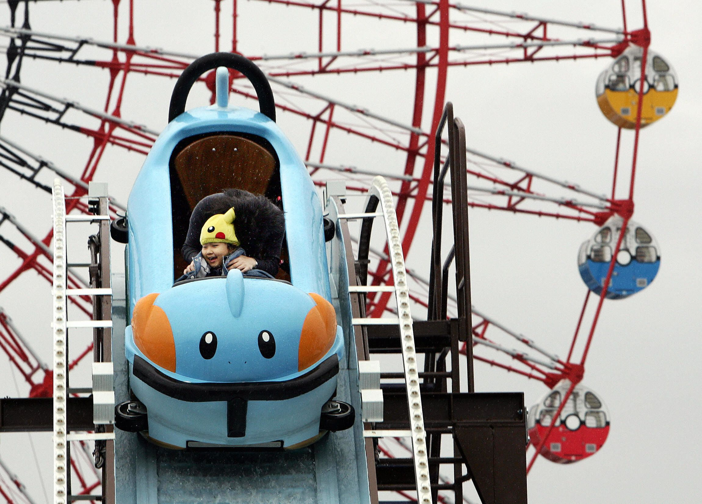 A small child in a Pikachu hat rides a roller coaster that looks like a Mudkip in a 2005 photograph.The Pokemon franchi