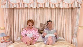 Mature couple in silk pyjamas reading on bed