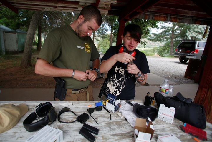 Matt Schlentz (L) and his partner Skylar Simon load magazines of ammunition during a firearms training class attended by memb