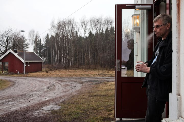 Bjorn, 54, who was sentenced to five and a half years for attempted murder, stands in front of the wooden cottage where he lives in Bastoy Prison on April 12, 2011.