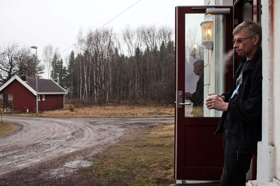 Bjorn, 54, who was sentenced to five and a half years for attempted murder, stands in front of the wooden cottage where