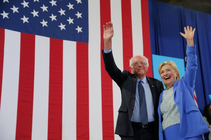 Democratic U.S. presidential candidates Hillary Clinton and Sen. Bernie Sanders stand together during a campaign rally where