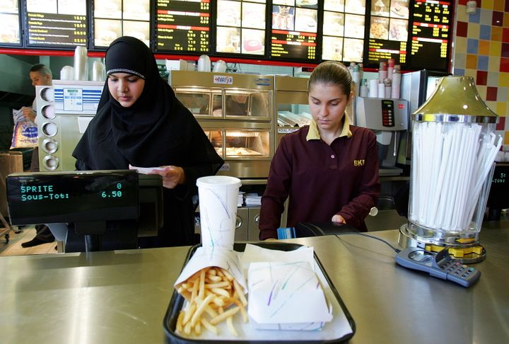 An employee (left), who gave her first name as Nora, prepares a food order at the counter of Beurger King Muslim, or BKM, in
