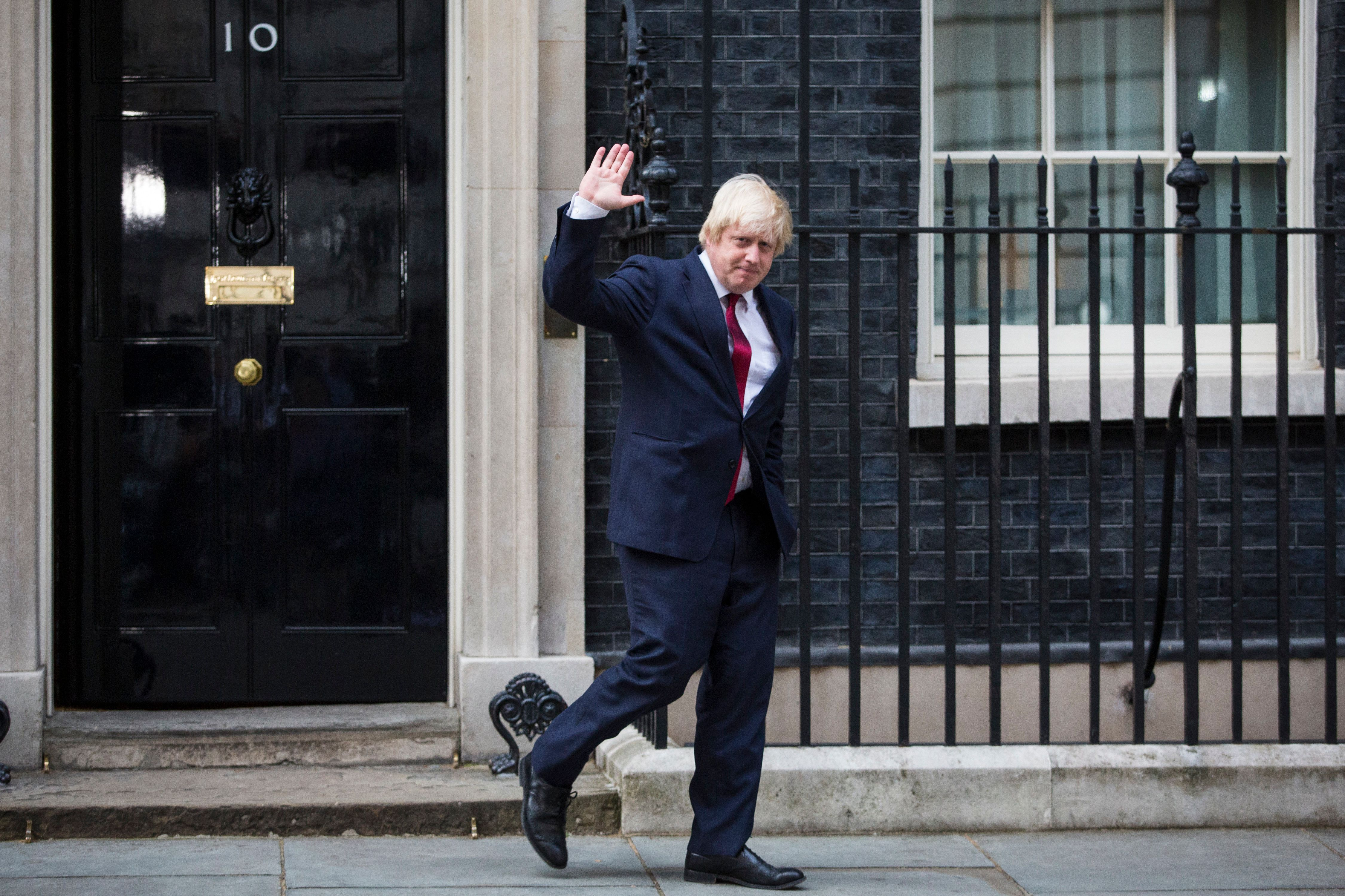 Boris Johnson waves as he leaves Downing Street after being appointed foreign