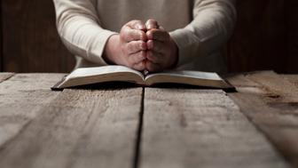 woman finger presses on bible book over wooden background