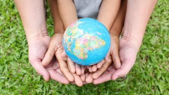 Hands holding the world on green grass background.