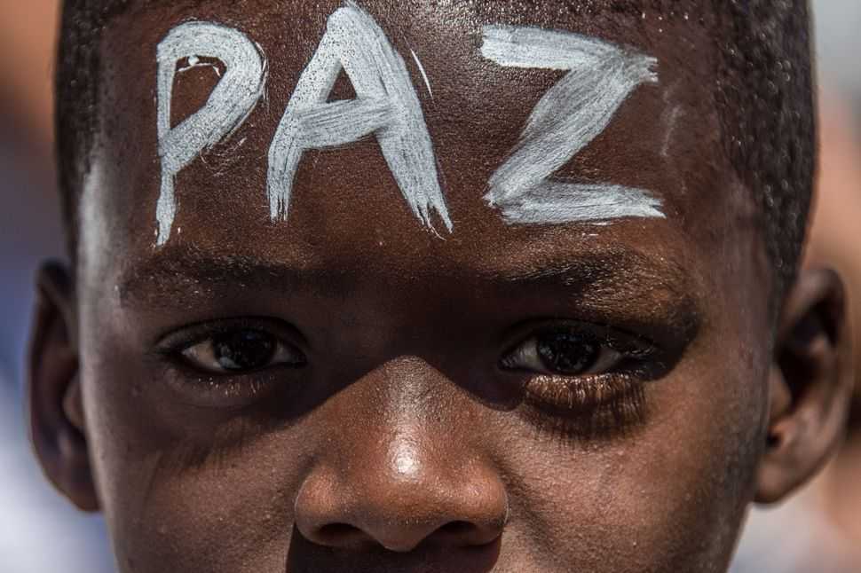 "A young Brazilian boy with the word ""peace"" written on his forehead protests in Rio's Alemao favela, where police s"