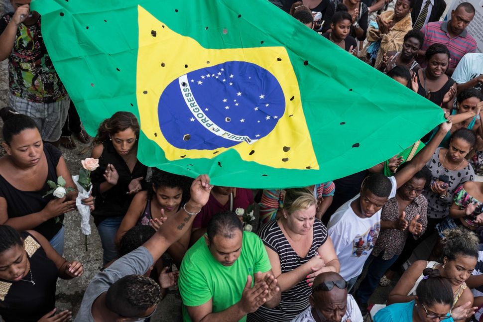 Protesters in Rio de Janeiro hold a Brazilian flag littered with holes to mark the number of shots fired at a group of young