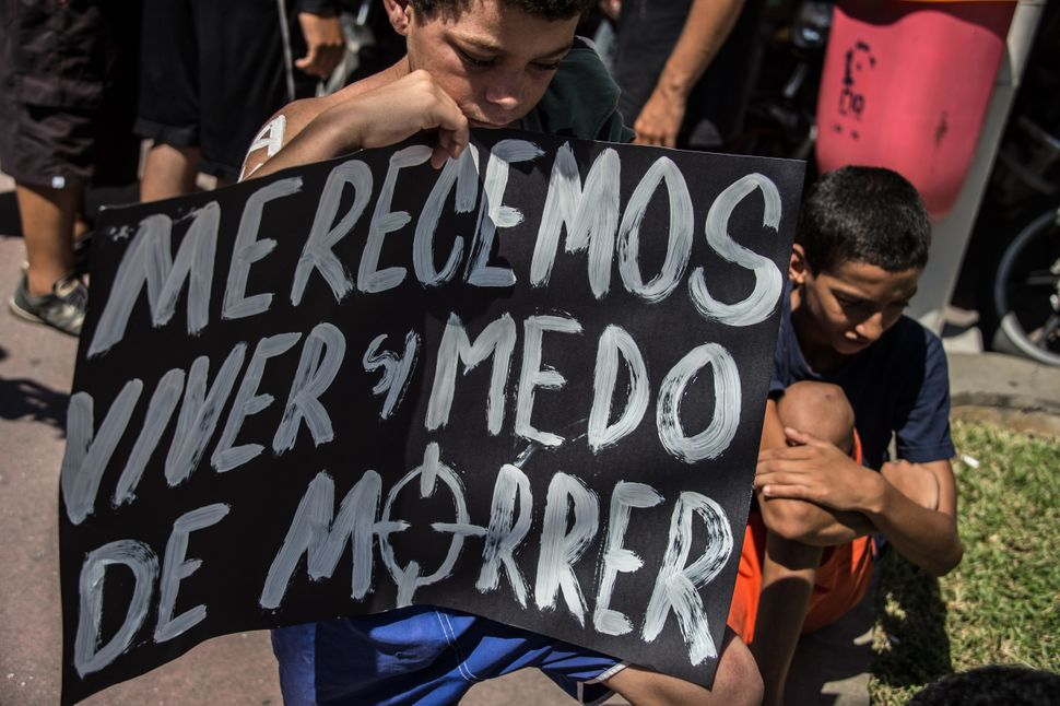 "A boy holds a sign that says ""We deserve to live without fear of dying,"" during a 2015 protest against police violence in Rio"