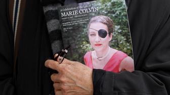 A man holds a sign honoring Sunday Times journalist Marie Colvin after a memorial service, outside St Martin in the Field in London May 16, 2012.  Colvin's final dispatch, published three days before she and a French photographer were killed by shell and rocket fire, came from a bleak cellar packed with women and children cowering in the besieged Syrian city of Homs.     REUTERS/Stefan Wermuth (BRITAIN - Tags: MEDIA CIVIL UNREST MILITARY SOCIETY OBITUARY)
