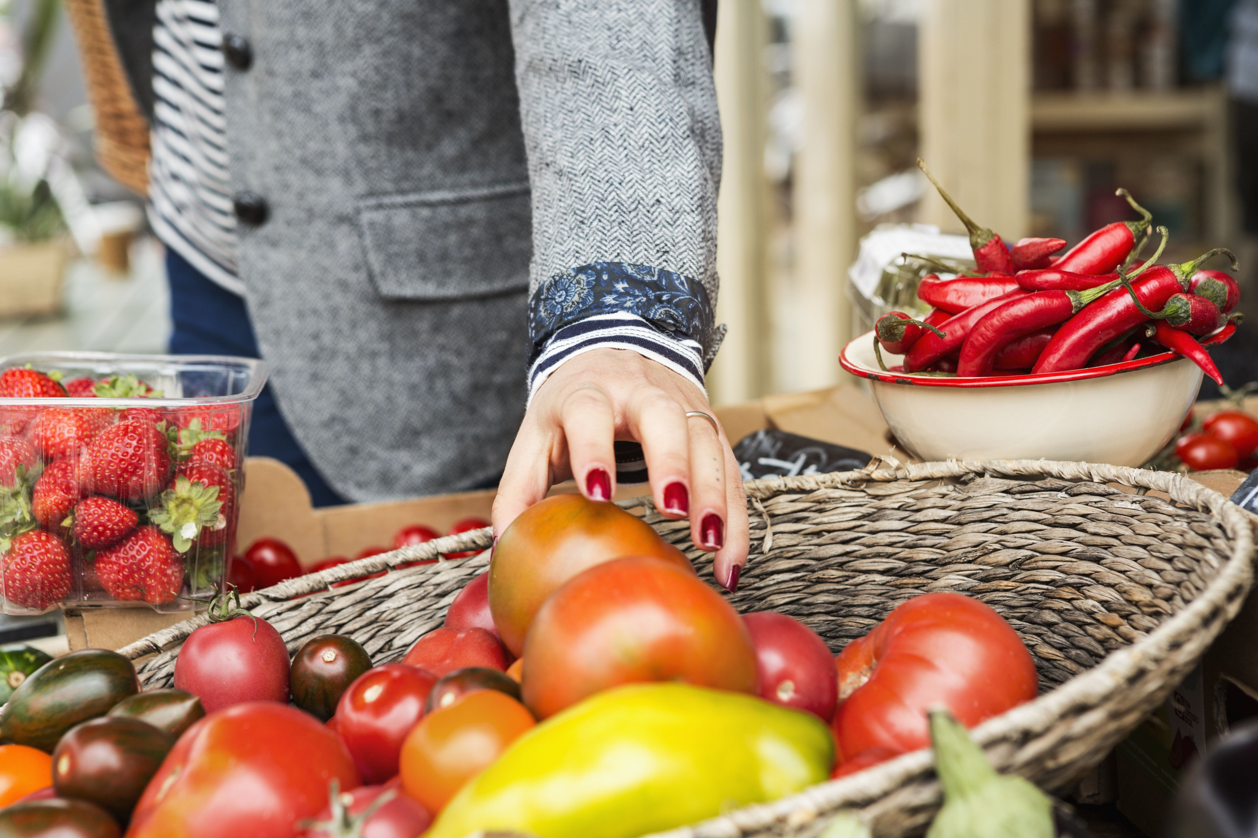 Close up of hand picking tomato from basket.