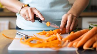 Woman cutting a carrot into slices
