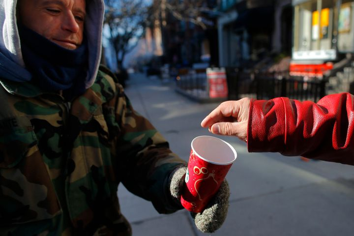 A passerby gives some money to a homeless veteran of the United States' wars in Iraq and Afghanistan, in Boston, Massachusett