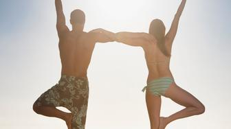 Couple balancing on one foot together at beach