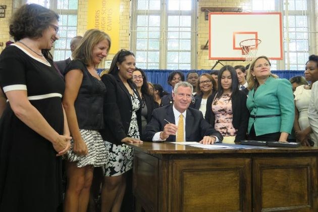 Mayor Bill de Blasio signing a package of legislation increasing access to feminine hygiene products...