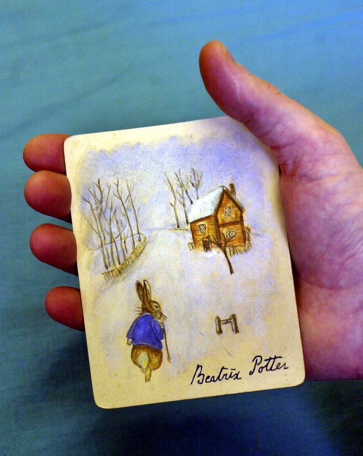 A rabbit in a blue jacket walking in snow toward a cottage at Dominic Winter Book Auctions in Swindon, England. The picture i