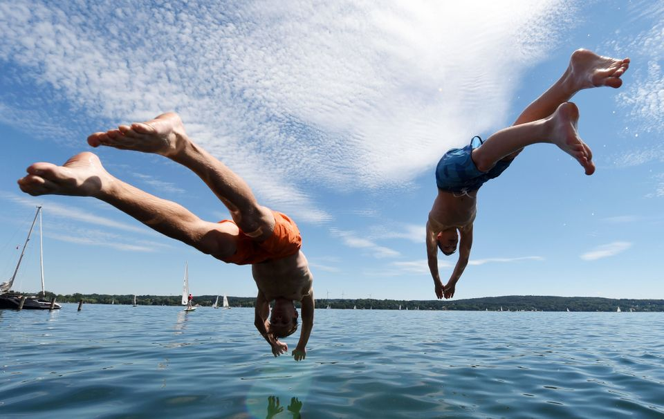 Two boys jump into the water of the Starnberger See lake in Starnberg, southern Germany, on July 10, 2016.