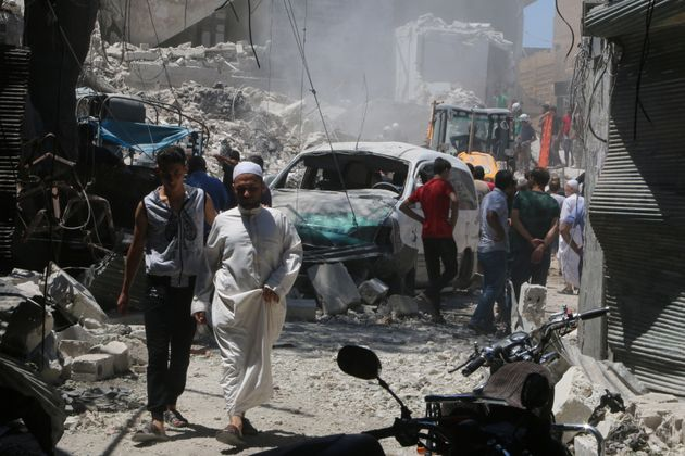Civilians inspect the damage of a barrel bombing in the Syrian city of Aleppo, north of Damascus. Syrian...